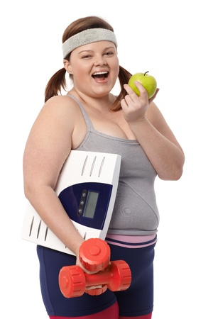 Plump woman biting green apple, holding dumbbells and scale, dieting, smiling. photo