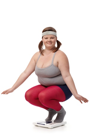 to crouch: Fat woman squatting on scale, smiling happily.
