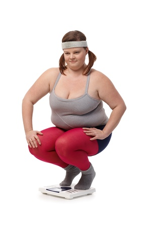 to crouch: Plump woman in sportswear squatting on scale disappointed.