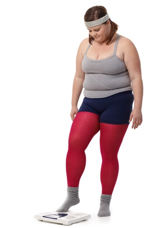 Fat woman in sportswear stepping on scale with fear. photo