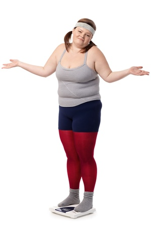 Fat woman standing on scale disappointed with opened arms, wearing sportswear. photo