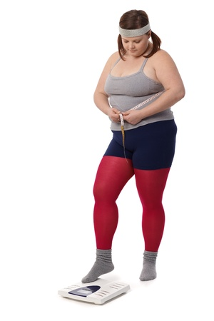Fat woman in sportswear measuring waistline and weight. photo