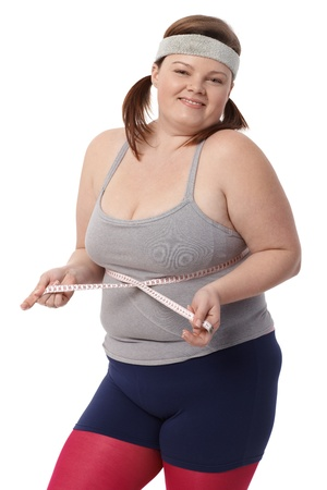 low fat diet: Happy fat woman measuring waistline by tape measure, smiling.