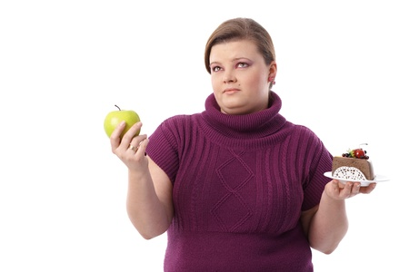 Overweight woman hesitating between green apple and chocolate cake. photo