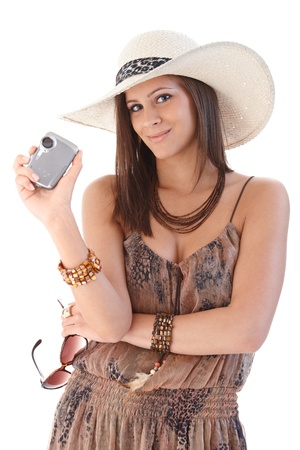Smiling woman holding camera, wearing hat at summertime. photo