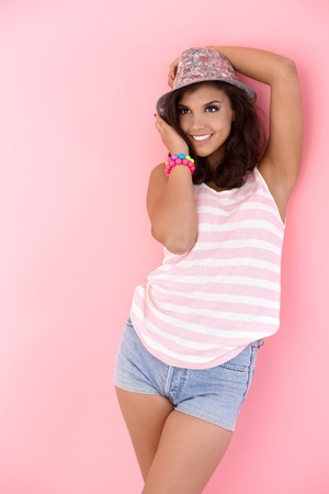 Teenage girl posing over pink background, smiling. photo