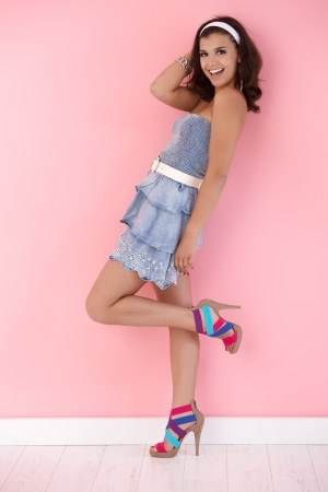 Happy girl posing over pink wall in mini dress and high heels. Stock Photo - 12652699