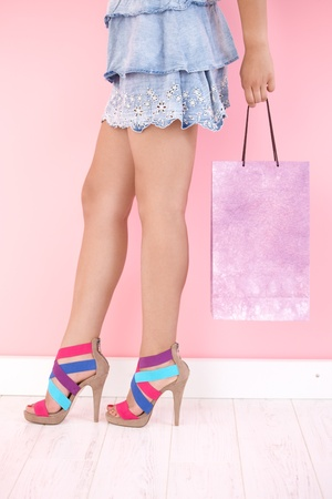 Sexy legs in mini skirt and multicolour sandals. photo