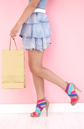 denim skirt: Pretty girl with shopping bag and high heels. Stock Photo