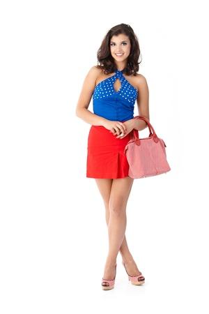 colegiala: Joven y bella mujer sonriendo en mini falda y tacones altos.