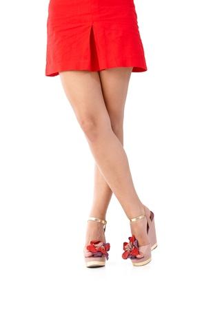 short skirt: Beautiful legs in red mini skirt and extraordinary high heel sandals. Stock Photo