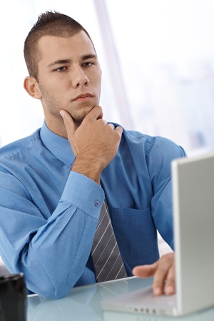 Serious young businessman at desk with laptop computer, thinking. Stock Photo - 12918554