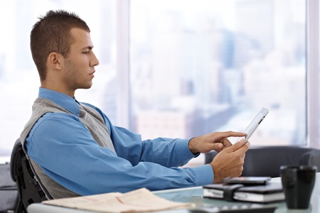 sitting at table: Serious young businessman sitting at skyscraper office desk, using tablet computer. Stock Photo
