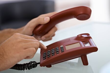 landline phone: Closeup portrait of male hand dial on red landline phone. Stock Photo