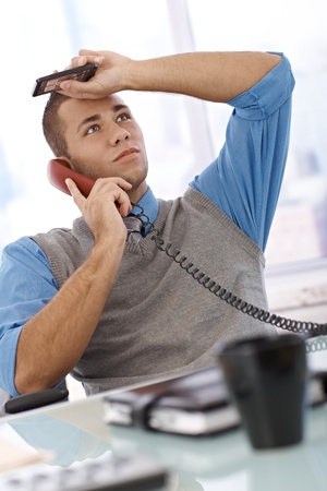 unsuccessful: Troubled businessman at desk concentrating on landline phone call, holding mobile phone, looking up.