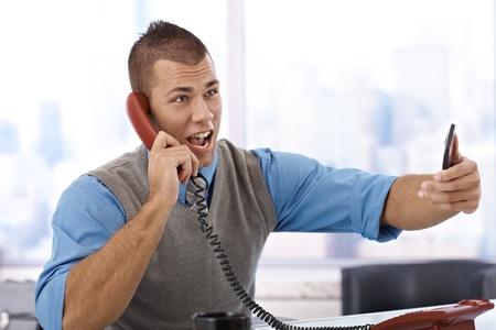 Angry young businessman shouting on landline phone in office, holding mobile phone. photo