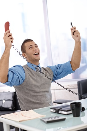 Happy businessman sitting at desk with arms raised, laughing, looking up, holding landline and mobile phone, celebrating. photo
