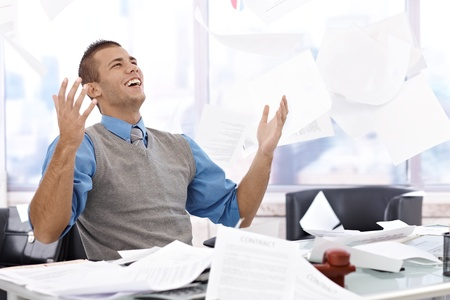 throw paper: Happy businessman sitting at desk, throwing documents up in air, laughing, celebrating.