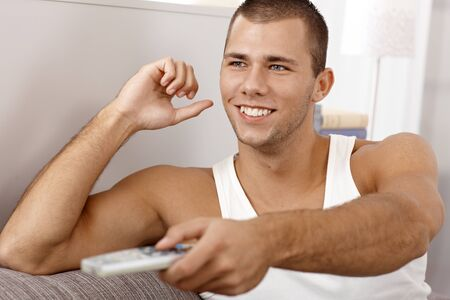 Happy young muscular man laughing at home, using remote control. photo