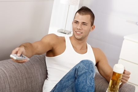 white singlet: Young sporty guy in undershirt on sofa with beer , using remote control, smiling. Stock Photo