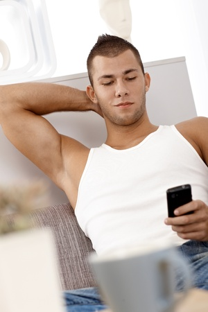 Muscular young guy wearing singlet texting on mobile phone, sitting on sofa, smiling confidently. photo