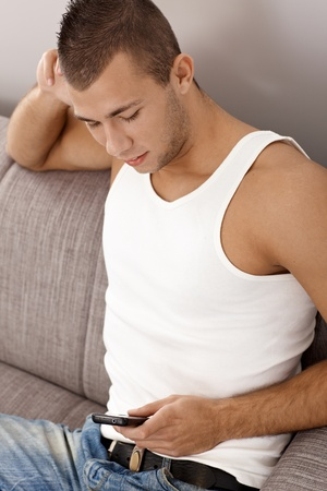 Portrait of young goodlooking guy in undershirt texting on mobile phone, sitting on couch. photo