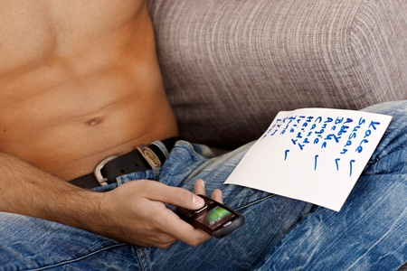 write off: Portrait of semi-nude athletic male body, using mobile phone and piece of paper with list of female names.