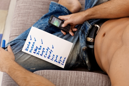 sms text: Sexy young semi-nude man sitting calling girls from list, names ticked off. Stock Photo