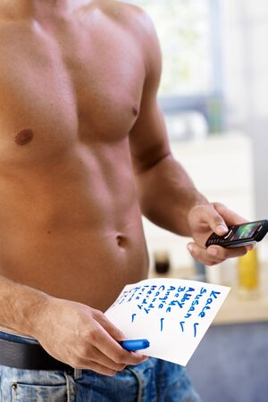 names: Semi-nude young man calling girls from list on paper, with mobile phone and pen handheld, names checked. Stock Photo