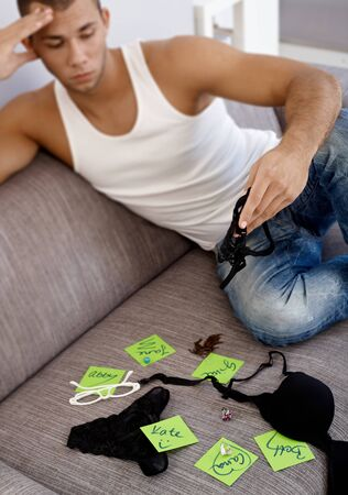 Hot young guy matching girls names on post-it notes with female jewelry accessories and underwear. photo