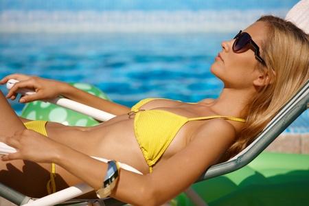Pretty woman sunbathing by pool in bikini, side view.