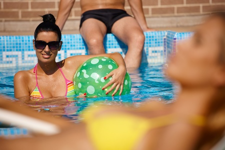 Attractive woman in outdoor pool at summertime, smiling. photo