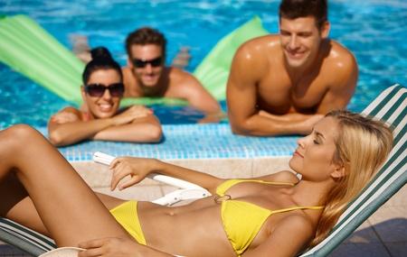 compa�erismo: Mujer atractiva y el compa�erismo en la piscina en verano.