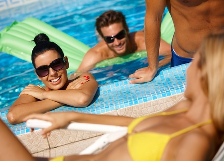 vibrant colors fun: Happy young companionship in swimming pool at summertime having fun.
