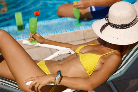 lay down: Sexy woman in bikini relaxing by pool, drinking cocktail, face covered with straw hat. Stock Photo