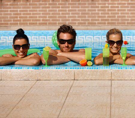 compa�erismo: C�ctel de camarader�a feliz beber en la piscina con una sonrisa.