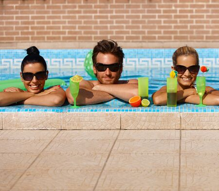 Happy companionship drinking cocktail in swimming pool, smiling. Stock Photo - 12918481