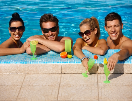 Beautiful young people having fun in swimming pool, drinking cocktail, smiling. photo