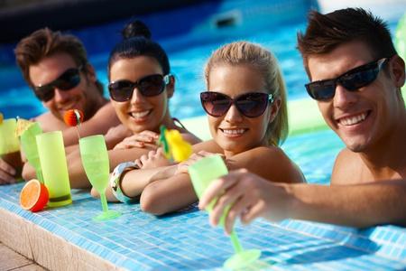Atractivas parejas jóvenes refrescantes en la piscina, cocktail de beber con una sonrisa.