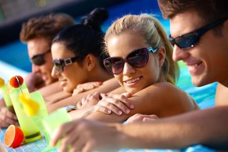 compa�erismo: Compa��a joven feliz en el agua, bebiendo c�cteles, sonriendo. Foto de archivo