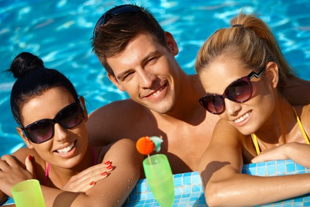 Attractive young people smiling in swimming pool, drinking cocktail. photo