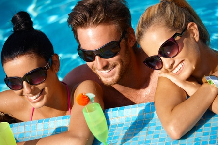 black man white woman: Young people having summer fun in outdoor pool, smiling.