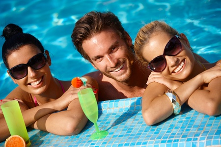 Happy young people on holiday, smiling in swimming pool. photo