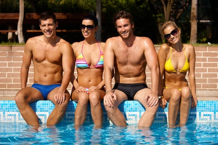 woman bathing: Attractive young people sitting by outdoor pool, smiling, looking at camera.