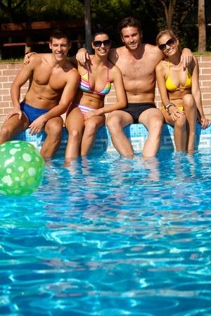 amigos abrazandose: El compañerismo feliz sentado en la piscina al aire libre en verano, sonriente.