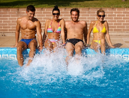 male friends: Attractive young people having summer fun by outdoor swimming pool, smiling.