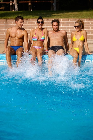 swimming shorts: Young people having fun in swimming pool on summer holiday, smiling.