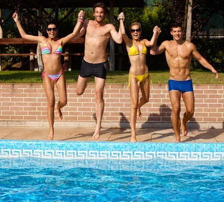 Happy young companionship jumping to outdoor swimming pool, having fun.