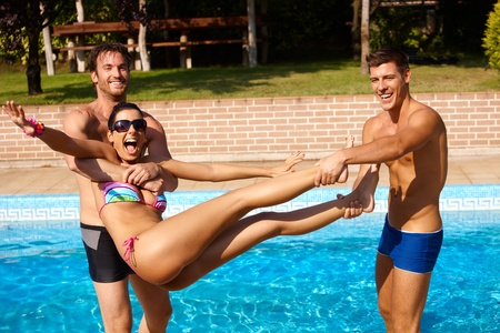 Young men throwing attractive girl into water at summertime, having fun. photo