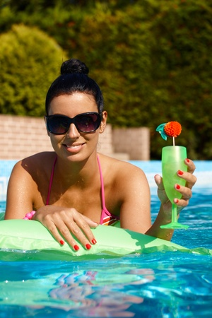 Attractive woman with cocktail in swimming pool, smiling. photo